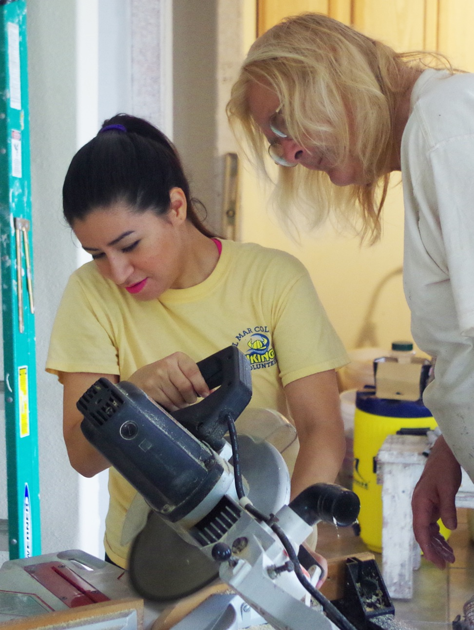 Erica Funes (left) gets help from Mari Randolph on how to properly use a miter saw on door trim pieces while helping build a Habitat for Humanity house.