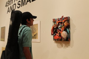 Texas A&M kingsville student Satyajith Akkinpally admires the art displayed at the art show on Feb 20.