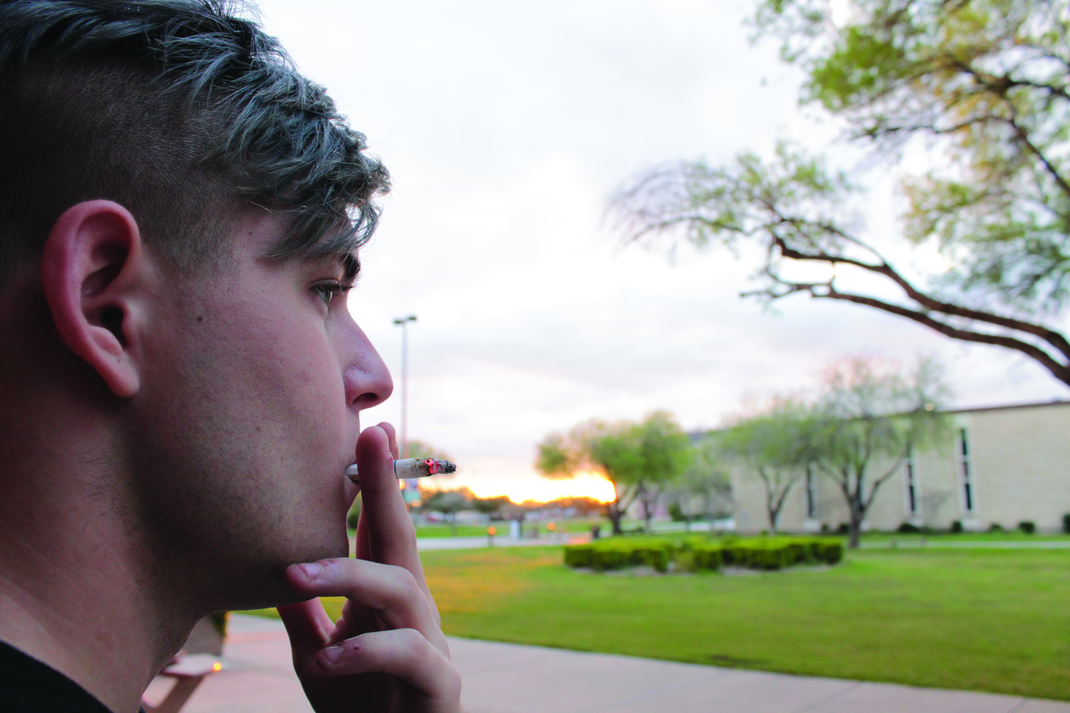 A student smokes on East Campus earlier this semester. Beginning in the fall, Del Mar College will ban all tobacco use on campus.