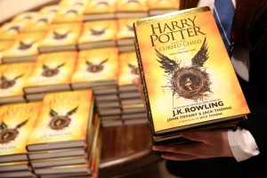 A store assistant holds copies of the book of the play of Harry Potter and the Cursed Child parts One and Two at a bookstore in London, Britain July 31, 2016. REUTERS/Neil Hall - RTSKER4