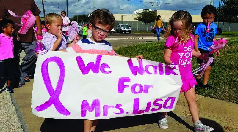 Gunn's students hold a banner they made for her as they march against breast cancer in her honor.
