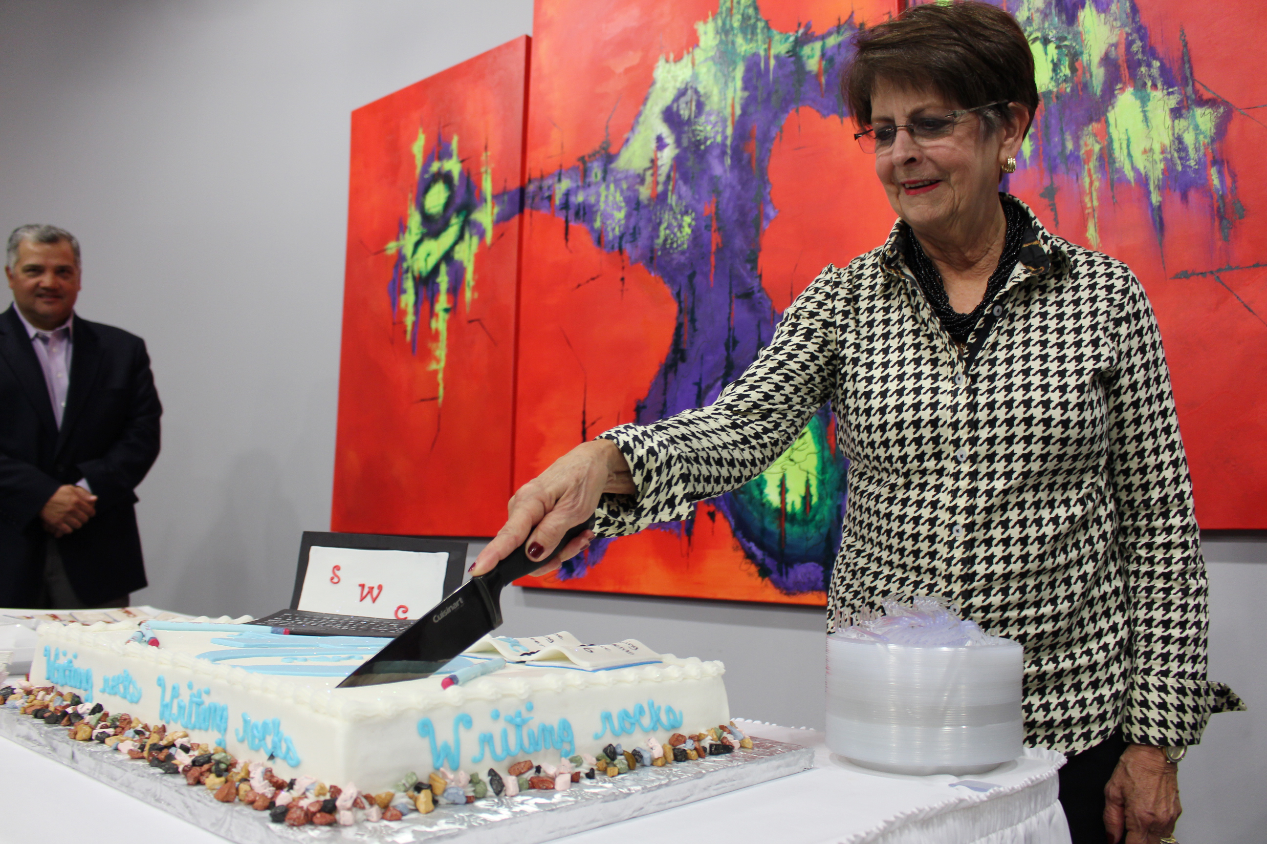 "Kay Stone Land as a honored guest cuts the cake at Stone Writing Center's ""40"" Celebration."