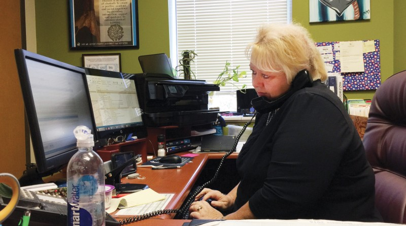 Tammy Micallef multitasks while working in her office at the Veterans Service Center.