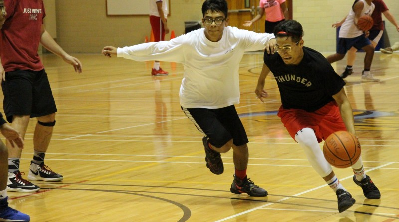 Joe Moreno covers Jonmichael Garza as he dribbles down the court during a 3-on-3 basketball game.