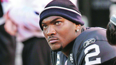 FILE - In this Nov. 30, 2008, file photo, Oakland Raiders quarterback JaMarcus Russell sits on the bench during an NFL football game against the Kansas City Chiefs in Oakland, Calif. The Raiders released former No. 1 overall pick Russell on Thursday, May 6, 2010, ending a three-year tenure marked by his high salary and unproductive play on the field. (AP Photo/Paul Sakuma, file)